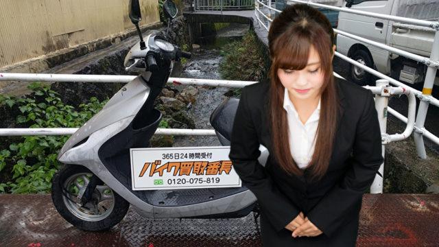 バイクの前でお辞儀する女性