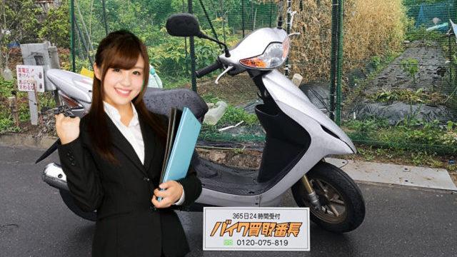 用箋ばさみを持つ女性とバイク